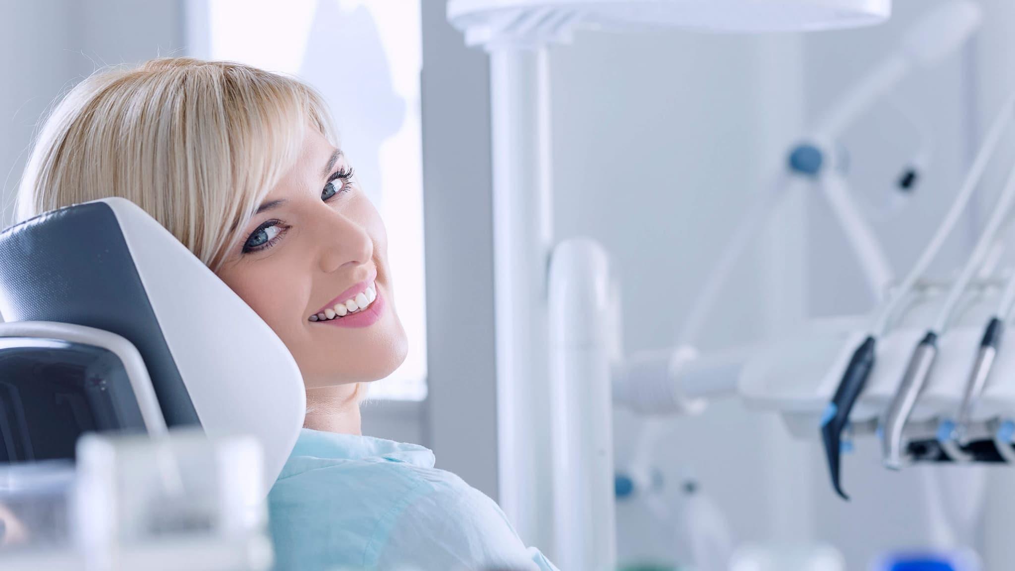 Frau auf Zahnarzt-Behandlungsstuhll vor Beratung zum Behandlungsablauf